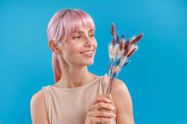 Радостная женщина с розовыми волосами улыбается и держит в руке сухоцветы нейтральных цветов, позируя