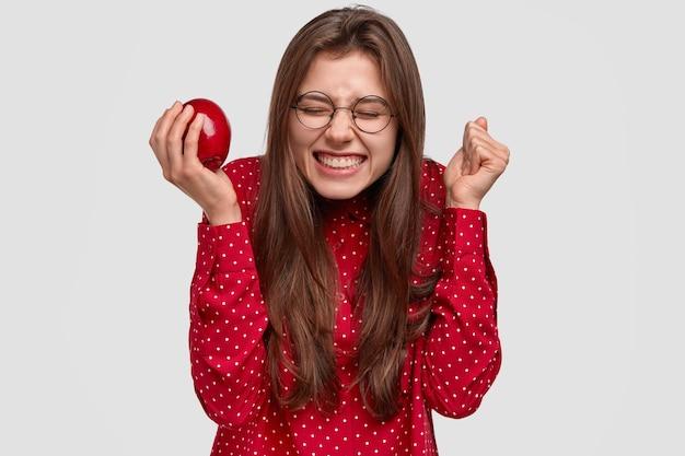 기뻐하는 표정으로 즐거운 여자, 주먹을 움켜 쥐고, 이빨 미소를 지으며, 무언가에서 즐거움을 느끼고, 신선한 사과를 먹고, 둥근 안경을 착용합니다.