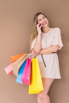 Joyful woman with shopping bags talking by phone