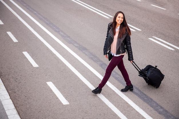 通りを渡るスーツケースを持つうれしそうな女性