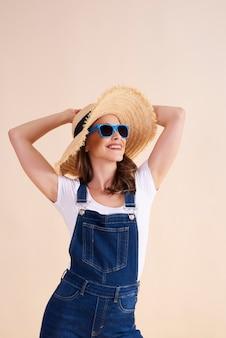 선글라스와 태양 모자를 쓴 즐거운 여자
