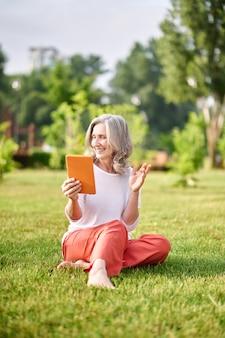 Joyful woman with tablet sitting on grass