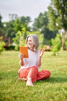 Радостная женщина с планшетом, сидя на траве