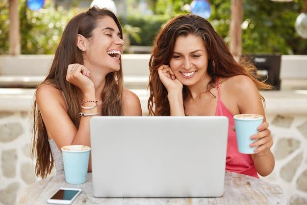 Веселые женщины веселятся вместе, смеются, смотря комедию онлайн на портативном компьютере, и отдыхают в летнем кафе, пьют горячий кофе или эспрессо.