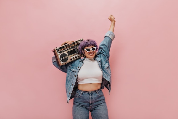 Donna meravigliosa e gioiosa con taglio di capelli corto viola in occhiali da sole triangolari e orecchini rotondi che si divertono sul rosa.