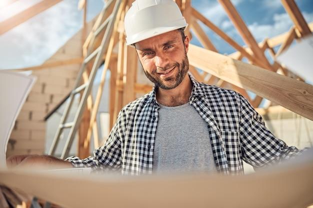 青写真を持っている建設現場のうれしそうな労働者
