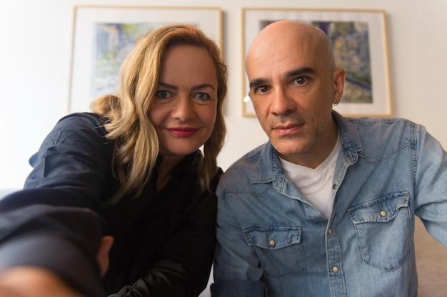 Joyful worried middle aged couple taking selfie