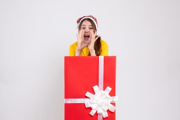 Радостная рождественская девушка в шляпе санта-клауса кричит, стоя за большим рождественским подарком на белом