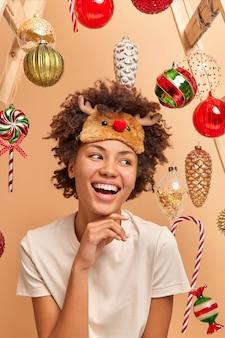 Gioiosa giovane donna afroamericana tiene la mano sotto il mento sorride a trentadue denti ha uno stato d'animo festivo andando ad appendere le palline di natale sull'abete gode di un'atmosfera festosa accogliente indossa maglietta e maschera per dormire