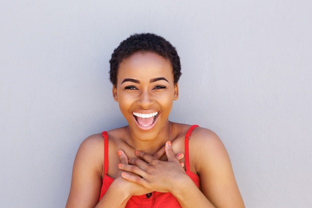 Joyful young african american woman laughing