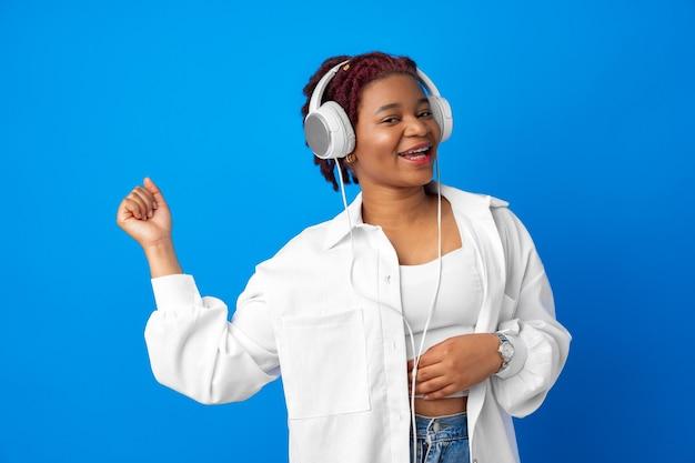 青い背景のヘッドフォンで音楽を聴いてうれしそうな若いアフリカ系アメリカ人女性