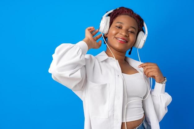 青い背景にヘッドフォンで音楽を聴いてうれしそうな若いアフリカ系アメリカ人女性