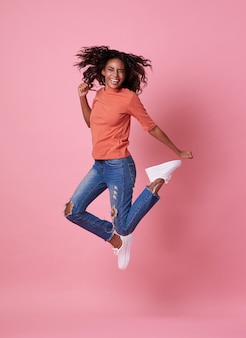 Joyful young african woman in orange shirt jumping and celebrating over pink.