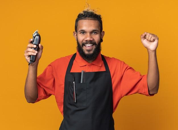 オレンジ色の壁に隔離された強いジェスチャーをしているバリカンを保持している制服を着ているうれしそうな若いアフリカ系アメリカ人の床屋