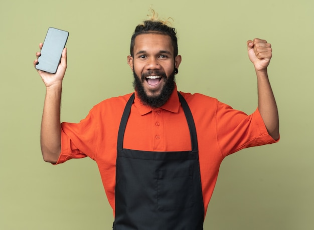 Joyful young afro-american barber wearing uniform holding mobile phone  doing yes gesture isolated on olive green wall