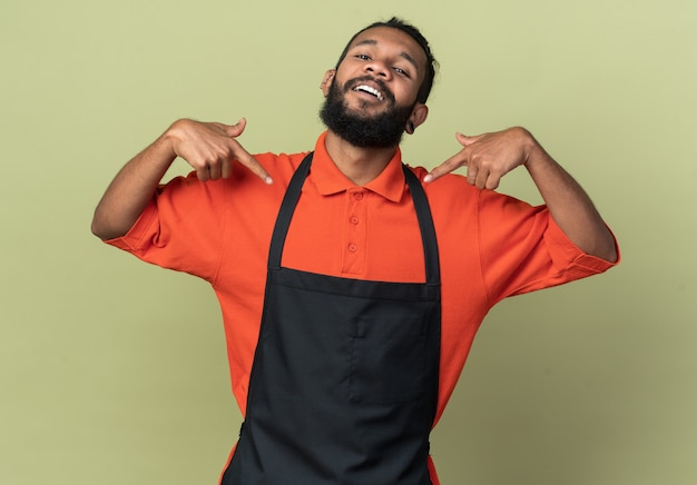 Радостный молодой афро-американский парикмахер в униформе, указывая на себя, изолированного на оливково-зеленой стене