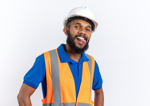 Joyful young afro-american builder man in uniform with safety helmet stucks out his tongue isolated on white background with copy space
