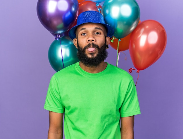 Joyful young afro-american guy wearing party hat standing in front balloons showing tongue