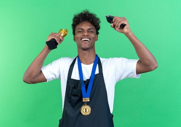 Радостный молодой афро-американский парикмахер-мужчина в униформе и кубке победителя повышения медали с машинками для стрижки волос, изолированными на зеленом фоне