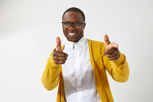 Joyful young afro american male hipster wearing stylish eyeglasses and cardigan smiling broadly, pointing index fingers , having positive friendly facial expression