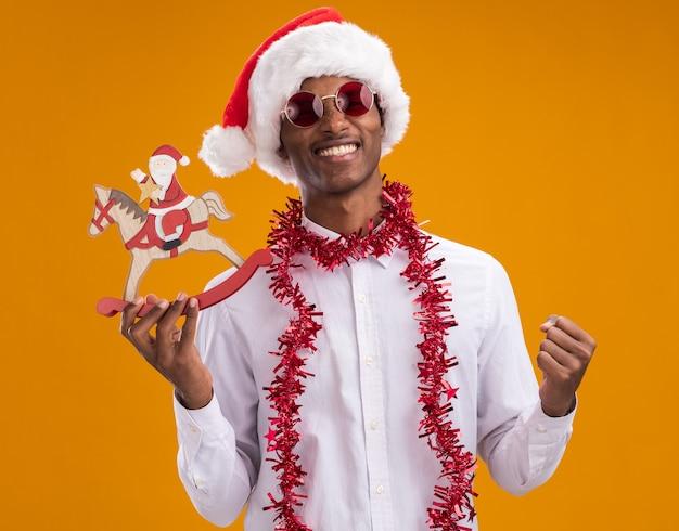 サンタの帽子とメガネを身に着けているうれしそうな若いアフリカ系アメリカ人の男は、オレンジ色の背景に分離されたはいジェスチャーをしているカメラを見て揺れる馬の置物にサンタを保持している首の周りに見掛け倒しの花輪