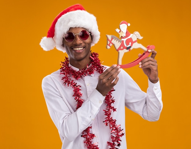 Joyful young afro-american man wearing santa hat and glasses with tinsel garland around neck holding santa on rocking horse figurine looking at camera isolated on orange background