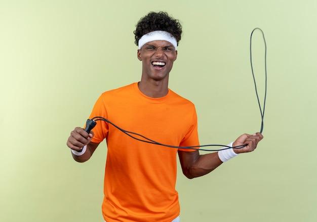 Gioioso giovane sportivo afroamericano che indossa la fascia e il braccialetto che tengono la corda per saltare
