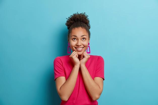 즐거운 젊은 아프리카 계 미국인 여성은 즐거움으로 위에 집중된 턱 아래에 손을 유지합니다.