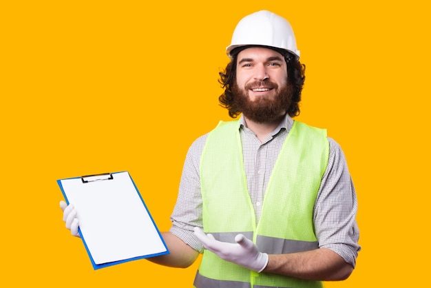 A joyful young architect is looking and smiling at the camera and holding his work pappers is pointing at them near a yellow wall