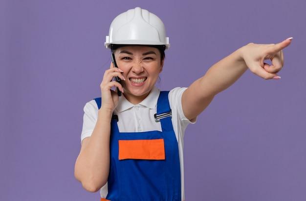 電話で話し、側を指している白い安全ヘルメットを持つうれしそうな若いアジアのビルダーの女性