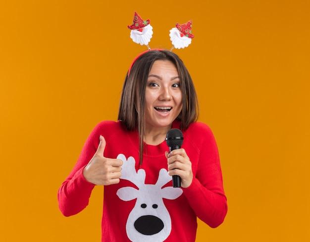 Радостная молодая азиатская девушка в рождественском обруче для волос со свитером говорит в микрофон, показывая большой палец вверх, изолированный на оранжевой стене