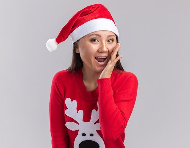 Радостная молодая азиатская девушка в новогодней шапке со свитером зовет кого-то изолированным на белом фоне
