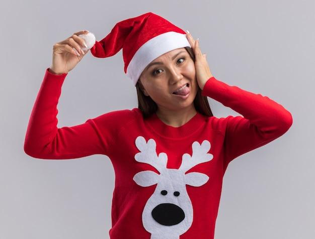 白い背景で隔離の舌を示すセーターとクリスマス帽子をかぶってうれしそうな若いアジアの女の子