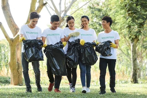 지역 공원에서 수집한 쓰레기가 든 가방을 들고 자원 봉사 셔츠를 입은 즐거운 아시아 젊은이들