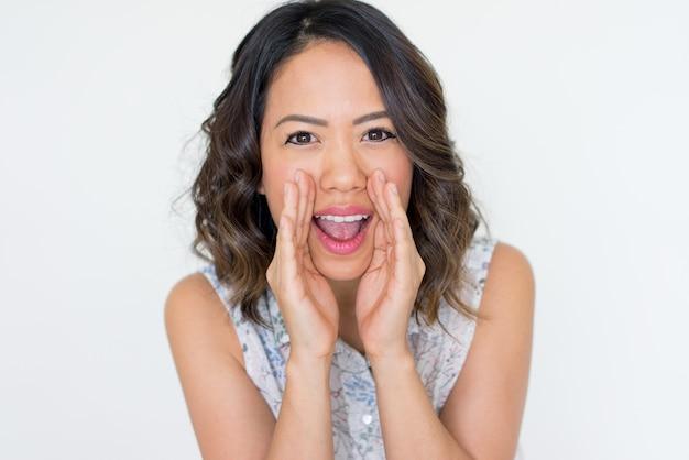 Joyful young asian woman shouting loud