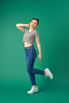 Радостная молодая азиатская женщина, стоящая на одной ноге. вид блаженной девушки, танцующей на зеленом.