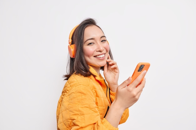 Joyful young asian woman stands sideways against white wall holds smartphone listens music via wireless headphones wears orange anorak enjoys favorite song uses special app on mobile phone
