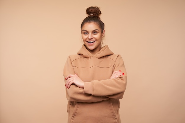 Joyful young attractive brown haired woman with natural makeup keeping her hands folded while posing over beige wall, being in nice mood and smiling cheerfully