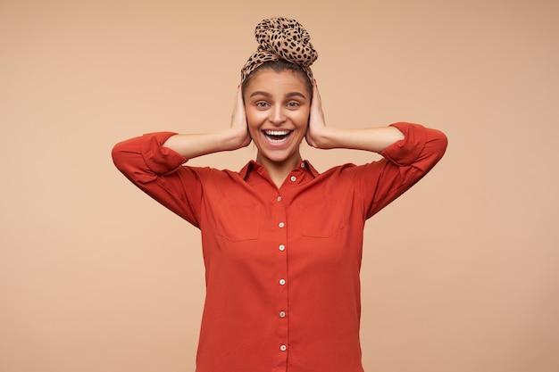Gioiosa giovane donna attraente del brunette con la fascia che tiene i palmi sollevati sulle orecchie mentre guarda eccitato davanti con un ampio sorriso, isolato sopra il muro beige