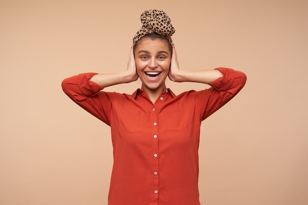 Радостная молодая привлекательная брюнетка с повязкой на голове, держащая поднятые ладони на ушах, взволнованно глядя вперед с широкой улыбкой, изолирована над бежевой стеной