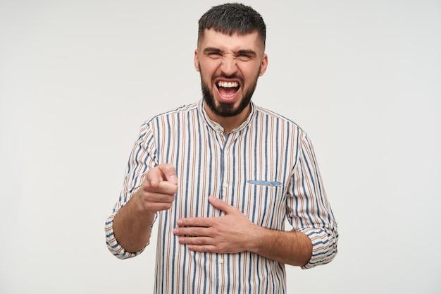 Радостный молодой привлекательный темноволосый бородатый мужчина, одетый в полосатую рубашку, хмурится, счастливо смеясь и указывая поднятым указательным пальцем, изолированно над белой стеной