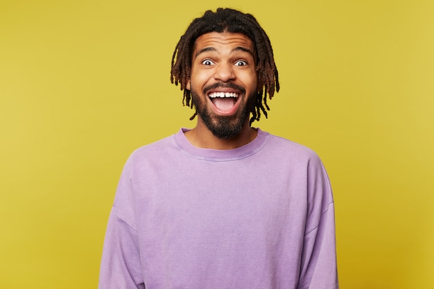 Joyful young attractive dark skinned brown haired man with dreadlocks looking surprisedly at camera with opened mouth while standing over yellow background Free Photo