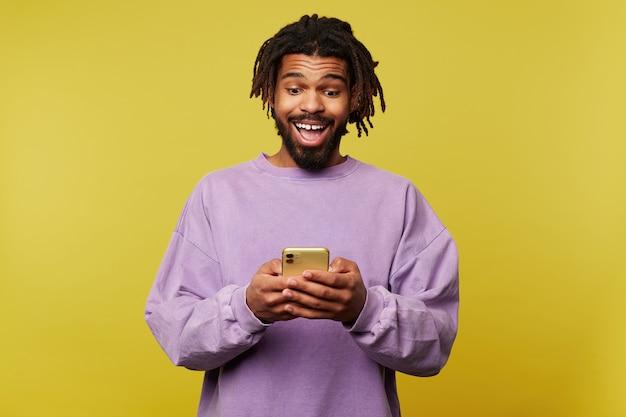 携帯電話を持って、黄色の背景の上にポーズをとって、広い口を開いて画面上で興奮して見ているひげを持つうれしそうな若い魅力的な暗い肌のブルネットの男