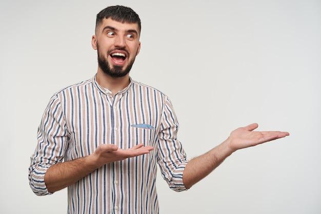 白い壁にポーズをとって、手のひらを上げて、広い笑顔で興奮して脇を見て、縞模様のシャツを着ているうれしそうな若い魅力的な短い髪のブルネットの男