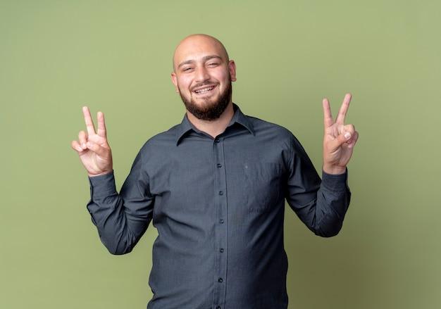 Uomo calvo giovane allegro della call center che fa segno di pace isolato su verde oliva