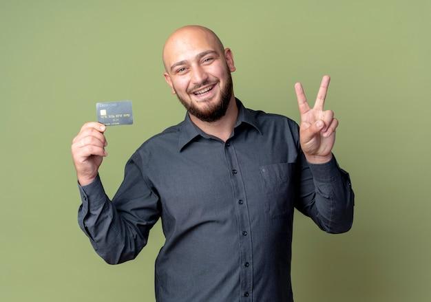 Gioioso giovane call center calvo uomo che tiene la carta di credito facendo segno di pace isolato su verde oliva