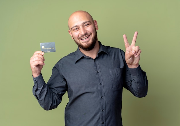 オリーブグリーンで隔離のピースサインをしているクレジットカードを保持しているうれしそうな若いハゲのコールセンターの男