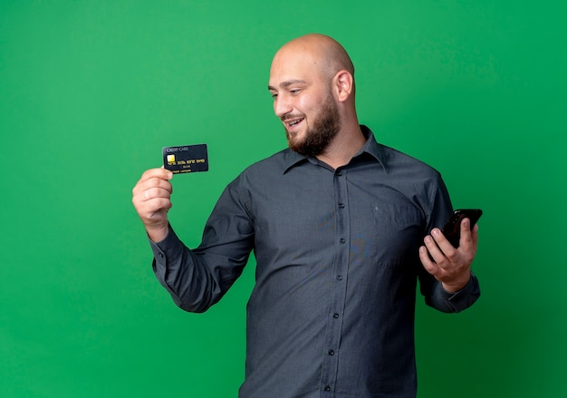 Uomo calvo giovane gioioso della call center che tiene la carta di credito e telefono cellulare che esamina carta isolata sul verde