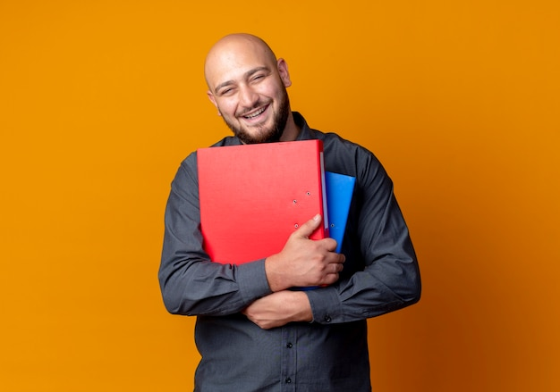 Uomo calvo giovane allegro della call center che tiene le cartelle isolate sull'arancio