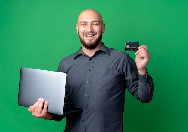 Joyful young bald call center man holding laptop and credit card isolated on green